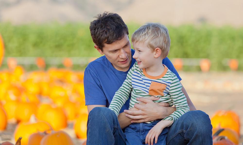 Papà e figlio in un campo di zucche